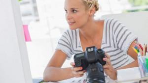 Frau mit Fotoapparat vor einem Bildschirm