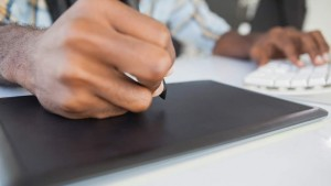 Mann hält Stift eines Grafiktabletts
